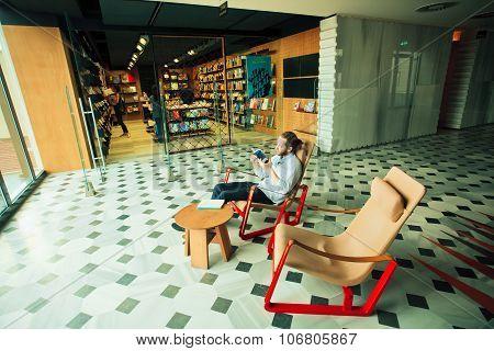 Young Man Reading A Book Near Bookstore Inside Modern Art Gallery