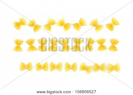 farfalle pasta arranged in a row string on white background