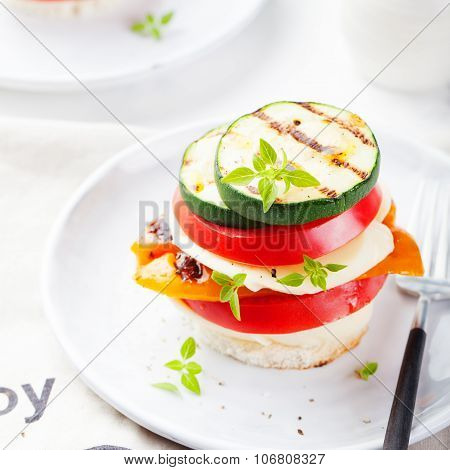 Grilled vegetables, cheese gratin stacked on a plate, fresh basil .
