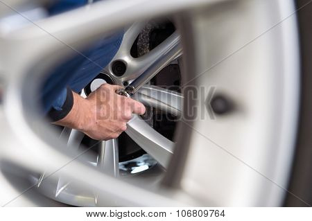 Mechanic changing tires at a tire service center, seen through the light weight alloy rim of a spare