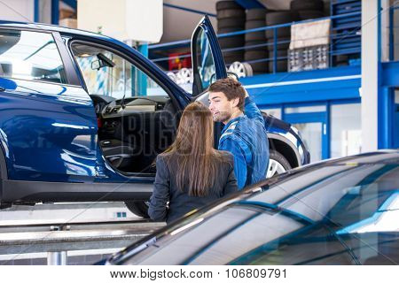 A sales mechanic shows the vehicle he has been working on to a business woman, who is interested in buying it at a used car dealership garage