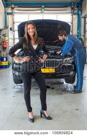 car sales woman, standing in front of a used car, which is serviced by a mechanic, ready to be sold at a dealership garage
