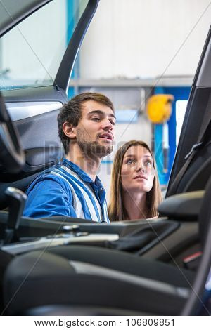 A sales mechanic, providing a woman with information about a lease car she is interested in. They're both standing in the door way at the passenger side of the vehicle