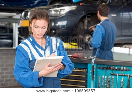 Two mechanics at work in a garage. A woman in front checks off a maintenance sheet for periodic examination or mot test, with a man in the background, working on repairing a brake disk of a vehicle