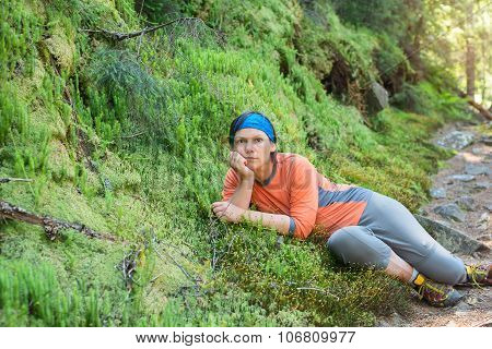 Hiker Woman Relaxing, Lying On The Green Moss, Looking At Camera, Deep In Thought.