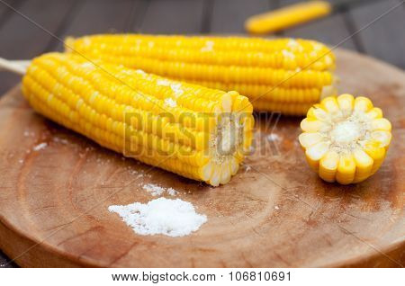 Boiled sweet corn cobs with salt on  wooden background