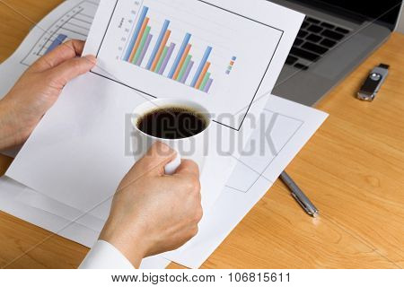 Female Hand Holding A Cup Of Coffee While Reviewing Financial Charts
