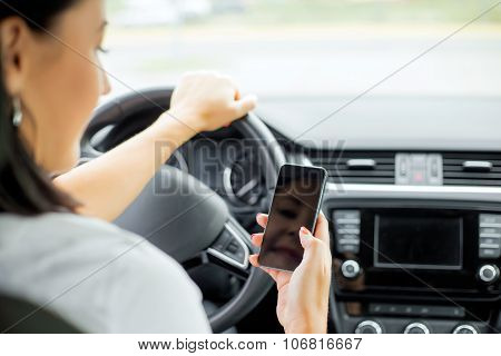 Woman driving and looking at cellphone