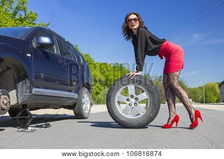 Leggy female changing wheel of car