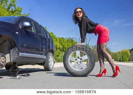 Leggy female changing wheel of car