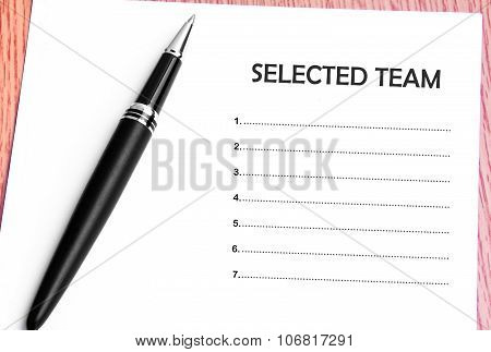 Pen  And Notes Paper With Selected Team List