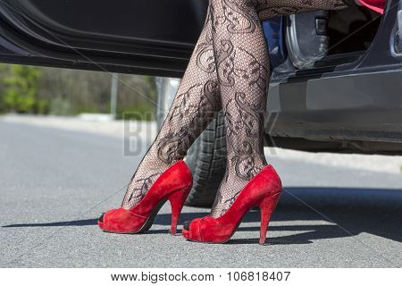 Feet of stylish female driver walking out of car