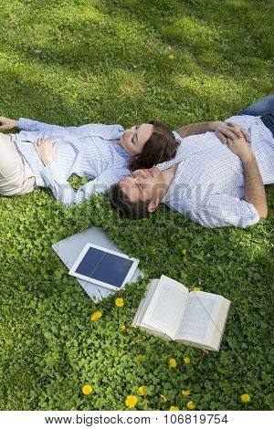 Young man and woman napping on grassy lawn
