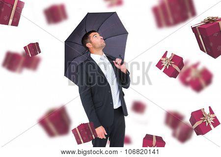 Businessman sheltering under black umbrella against red presents