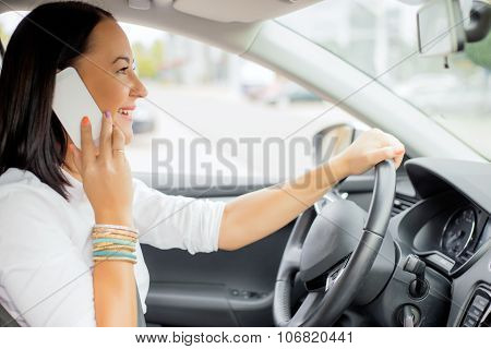 Woman driving and talking on the phone