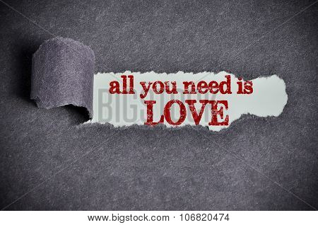All You Need Is Love Word Under Torn Black Sugar Paper
