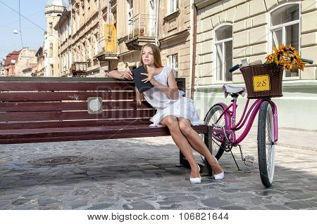 Girl With Bicycle Sitting On Bench And Reading Book