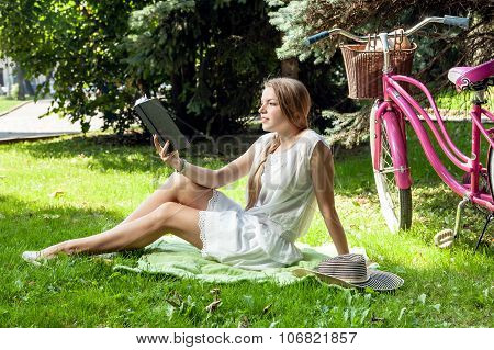 Woman Reads Book In City Park
