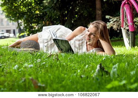 Woman Lays Reading Book In City Park