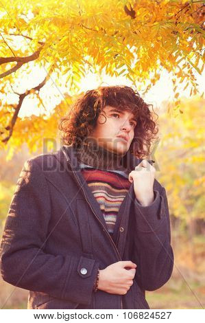 Young adult fashion man portrait dressed in gray jacket and striped sweater, oudoor in autumn park.