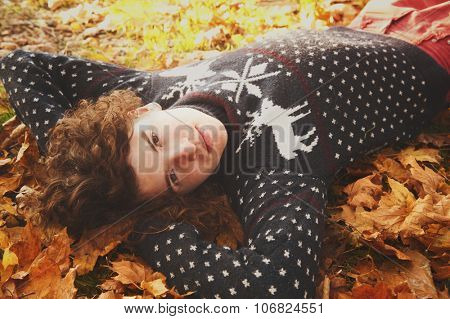 Young stylish smiling man dressed in knit sweater with deers lying on autumn leaves in park.