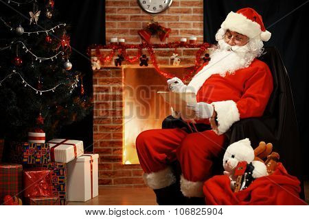 Portrait Of Happy Santa Claus Sitting At His Room At Home Near Christmas Tree And Big Sack And Readi