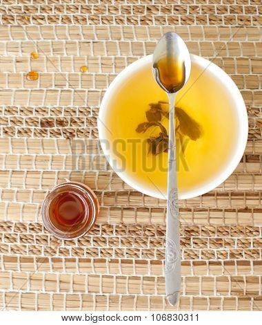 Green tea in a ceramic bowl with honey.