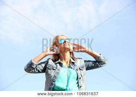 Yong woman listening to music on the sky background