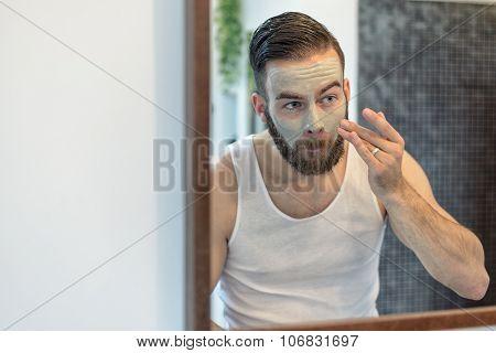 Bearded Man Applying A Face Mask