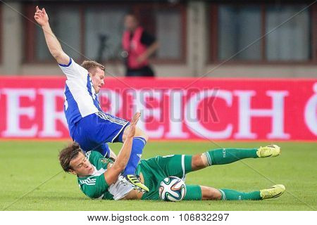 VIENNA, AUSTRIA - AUGUST 28, 2014: Sebastian Sorsa (#27 Helsinki) and Stefan Schwab (#8 Rapid) fight for the ball in an UEFA Europa League qualifying game.