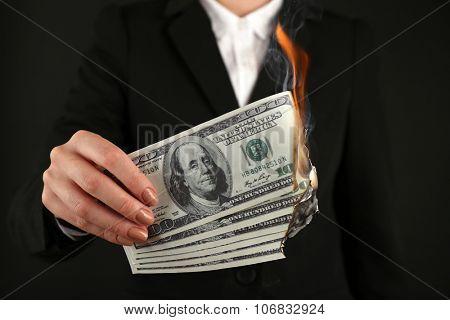 Woman burning  dollars closeup