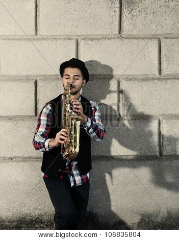 Handsome young man with sax on brick wall background