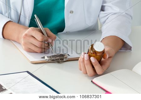 Close-up Of Doctor's Hands Writing Prescription And Holding Bottle With Pills