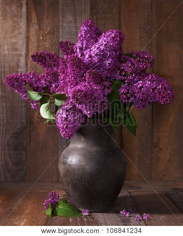 Bouquet of spring purple Lilac in old clay pot.