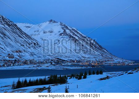 Siglufjordur at dusk in winter.Siglufjordur is a small fishing town in a narrow fjord  on the northern coast of Iceland.