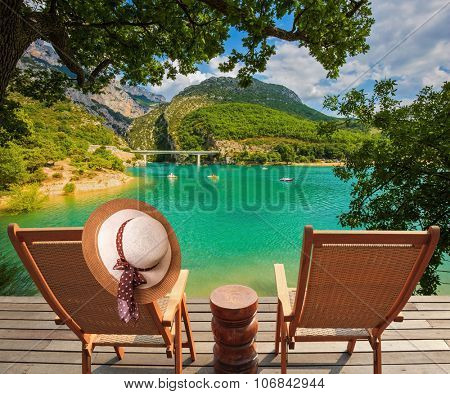 Travel to Provence. Two wooden chairs and straw hat on the platform at lake Verdon