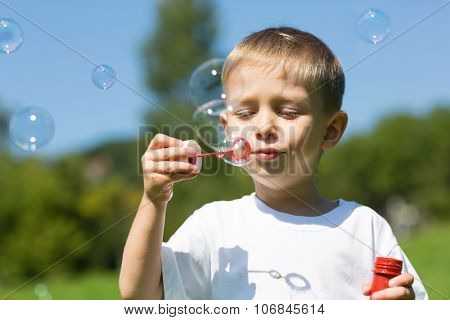 Cute boy blowing soap bubbles on a bright sunny day.