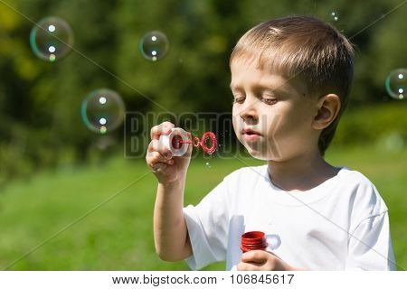 Cute boy blowing soap bubbles in a park in summer day