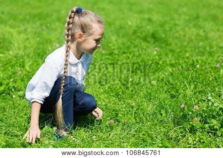 Girl with a scythe in the grass catches grasshopper