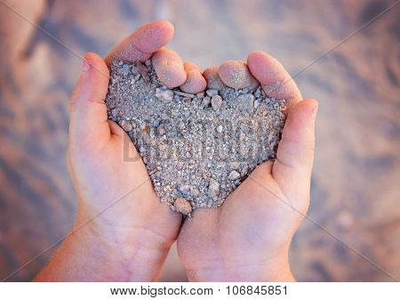 Young Girl Holding Gravel In Shape Of Heart (shallow Depth Of Field)