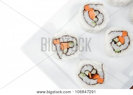Japanese Cuisine - California Roll with Cucumber , Cream Cheese and Raw Salmon inside. Served with wasabi . Isolated over white background on square plate