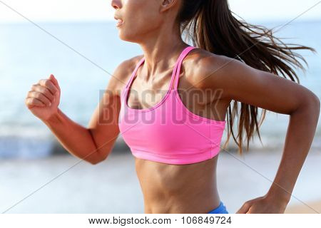 Running Determined Sprinting Woman Runner On Beach. Midsection of sporty woman training on beach. Young female is wearing pink sports bra. Determined runner is exercising on sunny day.