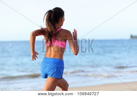 Fit young woman jogging on beach against sky. Rear view of determined female is in sports clothing. Runner is exercising at sea shore during sunny day.