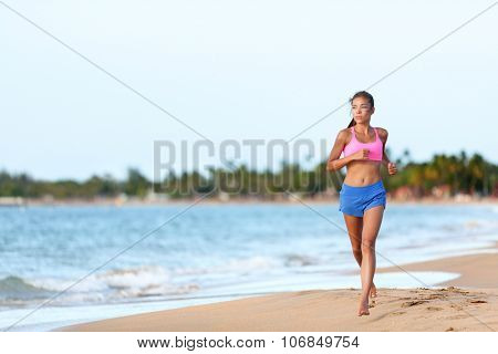 Young fit woman running on beach against sky. Full length of determined female runner in sports clothing. Jogger is exercising at sea shore during sunny day.
