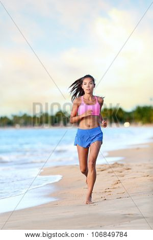 Confident young woman jogging on beach against sky. Full length of determined female is in sports clothing. Jogger is exercising at sea shore during sunny day.