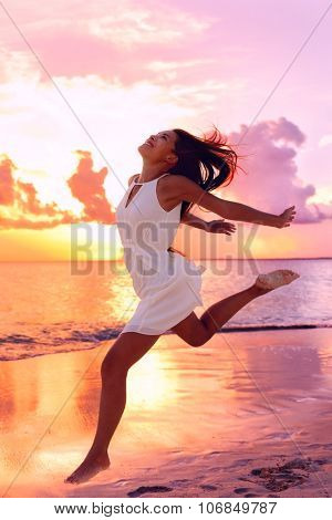 Carefree woman jumping at beach during sunset. Full length of female is wearing sundress. Tourist is enjoying vacation against orange sky at sea shore.