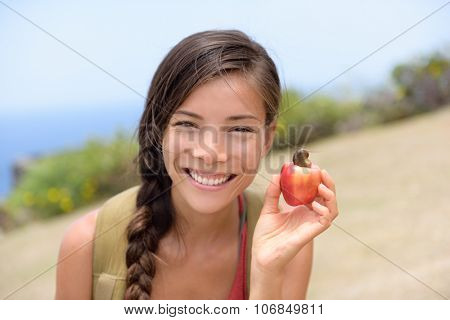 Girl showing natural fresh cashew nut apple fruit. Asian Chinese woman portrait smiling holding a freshly picked apple fruit from the tropical tree where the cashew nut come from. Caribbean food.