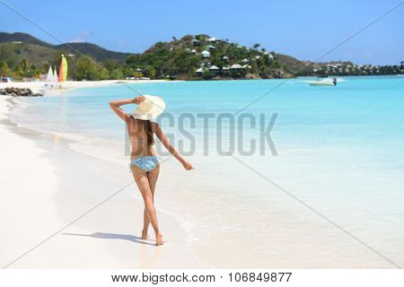 Beach travel vacation woman in bikini wearing beach hat, joyful and free on holidays on Jolly Beach, Antigua Girl on travel vacation holidays having fun. Asian Chinese Caucasian female model.