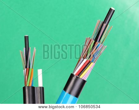 Two fiber optic loose tube cables with stripped ends and bare exposed colored optical fibers