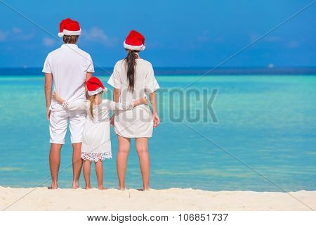 Happy family of three in Santa Hats on beach during Christmas vacation